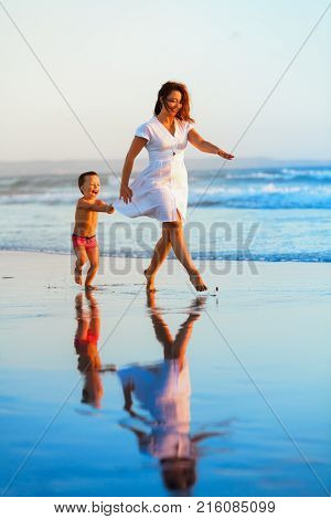 Happy family - mother baby son have fun together barefoot child run with splashes by water pool along sunset sea surf on black sand beach. Travel lifestyle parents with kids on summer holiday.