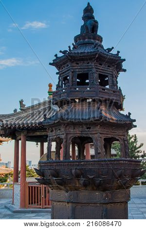 A pagoda shaped fire pit in a temple's frount court yard blackened from years burning offerings during various ceremonies.