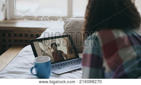 Curly young woman having online video chat with friend using laptop camera while lying on bed at home