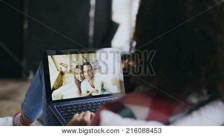 Curly young woman having video chat with friends using laptop camera while lying on bed at home