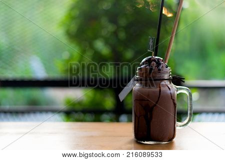 Summer ice fresh drink. Chocolate milkshake with ice cream and whipped cream marshmallow served in glass mason jar green nature background copy space