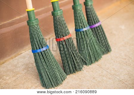 Four New Brooms Made Of Green Plastic.