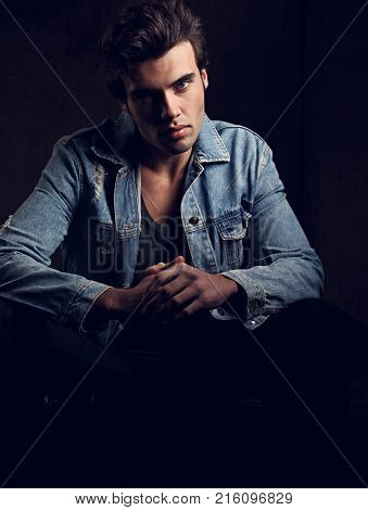 Handsome Male Model Posing In Fashion Blue Jeans Jacket Looking On Dark Shadow Background. Closeup T