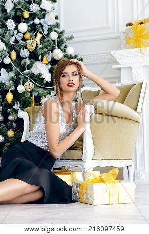 Christmas, winter holidays concept. Beautiful charming woman in evening dress. Luxurious apartments decorated for Christmas. Beauty, fashion.