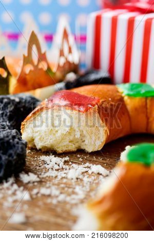 closeup of a roscon de reyes, the traditional spanish three kings cake eaten on epiphany day, and some pieces of candy coal on a rustic wooden table