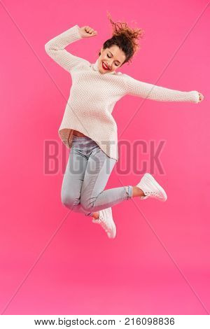 Full length portrait of a happy excited girl celebrating success and jumping isolated over pink background