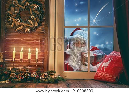 Merry Christmas! Santa Claus is knocking at window. Room decorated for holidays. View indoors home.