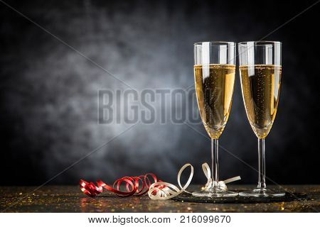 Two champagne glasses in golden glitter
