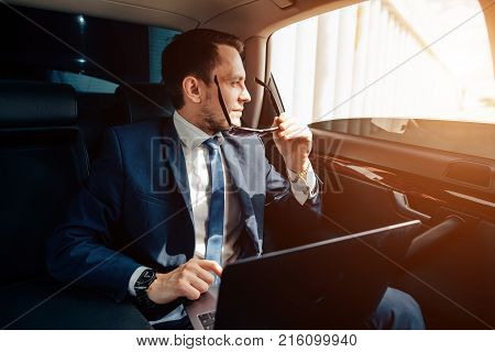 young stylish businessman in sunglasses on backseat of car.