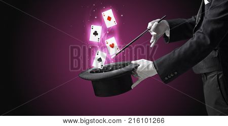 Magician with white gloves conjuring playing cards from a cylinder with magic wand