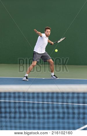 Professional tennis player athlete man hitting forehand ball over net on hard court playing tennis match. Sport game fitness lifestyle.