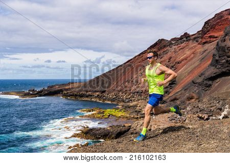 Man trail running in the mountain hills nature landscape. Ultra runner competing on cross country race working out endurance on volcanic rocks outdoor path.