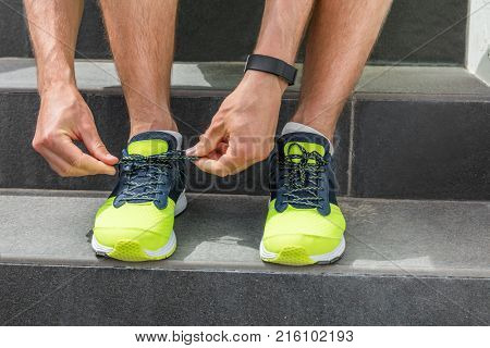 Sport man tying running shoes laces getting ready going to the gym workout wearing smartwatch for training cardio exercise on stairs. Acitve healthy lifestyle athlete, fitness motivation.