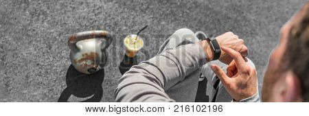 Fitness app fit man using sport smartwatch at gym. Closup of smart watch with kettlebell weight and juice fruit smoothie for healthy active urban lifestyle. Banner panoramic crop.