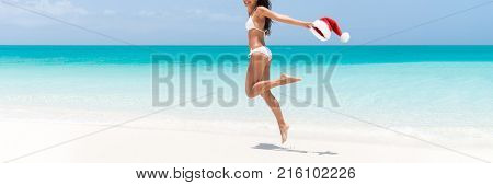 Christmas Santa woman with lean legs and healthy body jumping of joy on tropical vacation beach. Sexy bikini girl happy running in Caribbean. Panorama banner.