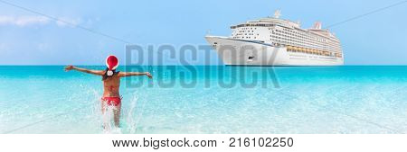Christmas cruise travel vacation holidays in Caribbean beach. Happy bikini woman wearing santa claus hat on new year holiday running in happiness in blue turquoise water with ship in background.
