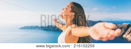 Europe cruise Santorini travel free woman banner. Greece vacation carefree freedom with open arms in famous travel holiday. Elegant Asian girl on greek travel luxury resort in Oia Santorini.
