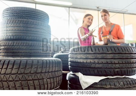 Helpful experienced female auto mechanic checking the identification number of a tire for a customer in an automobile repair shop with various tires for sale