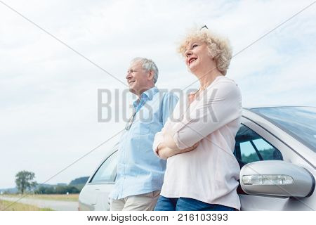 Low-angle view portrait of two senior people smiling and looking away with confidence and positive attitude while leaning on their car
