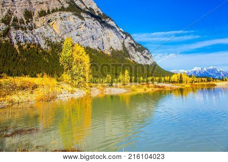 Rocky Mountains are reflected in the smooth water of Lake Abraham. Indian Summer in the Rockies of Canada. Concept of ecological and active tourism