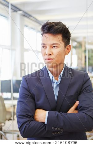 Young asian as businessman thinking with scepticism and arms crossed