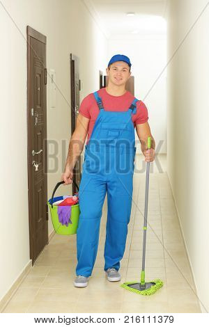 Young man with cleaning supplies in hall