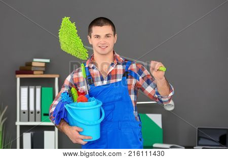 Young man with cleaning supplies in office