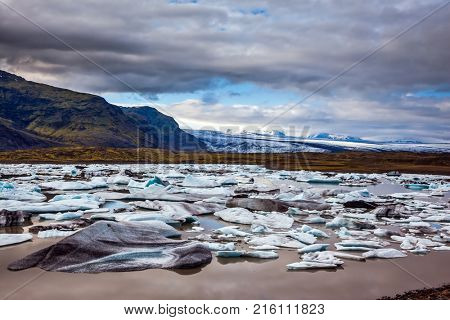 Summer in Iceland. The concept of extreme northern tourism. The picturesque lake with splinters of ice floes formed by thawed snow of grand glacier Vatnajokull