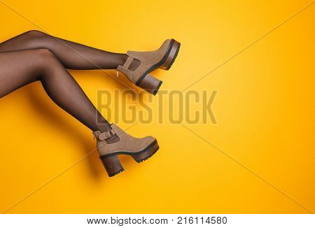 Young woman in stylish shoes on color background