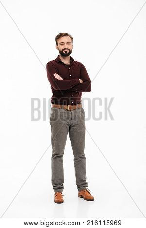 Full length portrait of a confident young man standing with arms folded isolated over white background