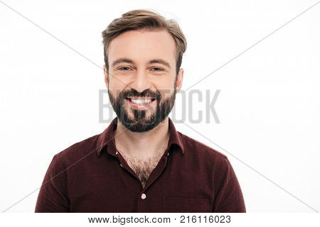 Close up portrait of a smiling young bearded man looking at camera and laughing isolated over white background