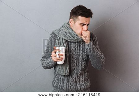 Sick Man in sweater and scarf holding cup of tea while having cough over gray background