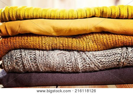 Beautiful Photo Of A Pile Of Knitted Yellow Woman Sweaters. Woman Fashion. Autumn Clothing.