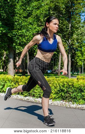 Young sportive teen in a bright blue sport bra and black leggings running in the nature. Photo of an athlete girl with a beautiful sports body