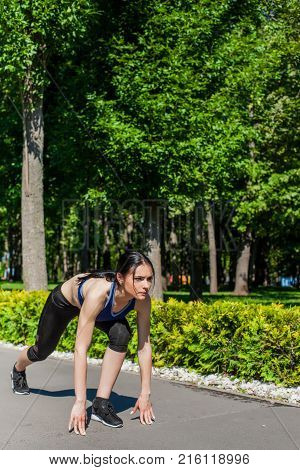 Young sportive girl in a bright blue sport bra and black leggings starting running in the park. Photo of an athlete girl with a beautiful sports body