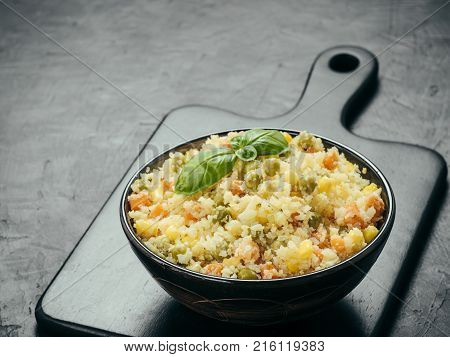 Close up view of cauliflower rice with vegetables and spices on black cutting board over black concrete background. Cauliflower Rice with corn, green pea and carrot, Paleo diet. Copy space.