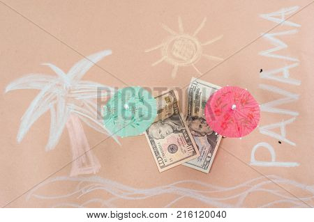The concept of offshore banking and tax havens. Picture with dollar bills on a tropical beach, under a palm tree and an umbrella