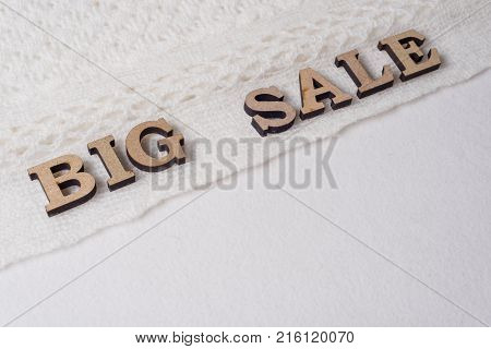Word BIG SALE abstract wooden letters, background textured winter light knitted woolen