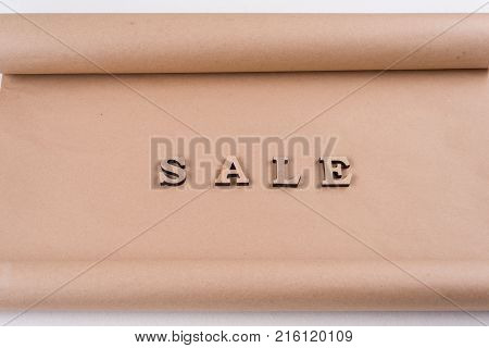 Word SALE abstract wooden letters, background vintage kraft paper