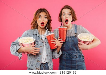 Photo of two shocked women friends standing isolated over pink background. Looking camera eating popcorn watch film drinking aerated sweet water.