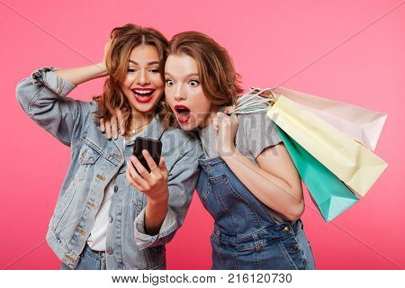 Image of shocked two women friends standing isolated over pink background. Looking aside holding shopping bags using mobile phone.