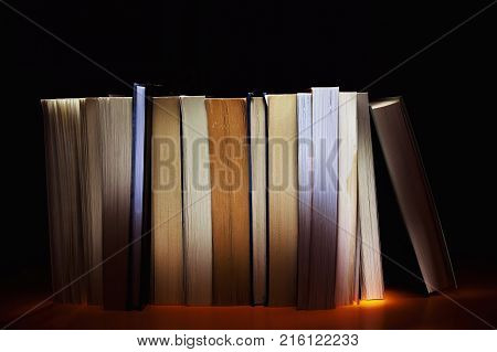 Group of various books on orange surface.