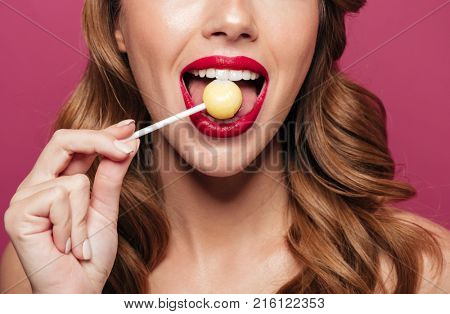 Cropped photo of petty brunette lady with make up and styling lick lollipop like watermelon isolated over pink