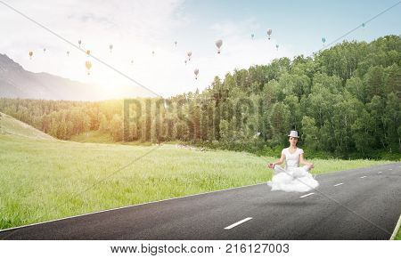 Young woman keeping eyes closed and looking concentrated while meditating on cloud above the road with beautiful and breathtaking landscape on background.