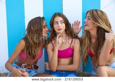 Three teen best friends girls funny whispering gesture in a beach stripes background