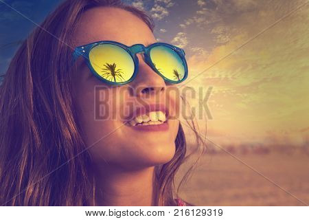 Brunette girl on beach sunglasses with palm tree reflection filtered image