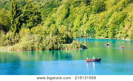 Plitvice Lakes National Park, Croatia - August 30, 2017: Park visitors enjoying evening row boat ride on a lake in Plitvice Lakes National Park, Croatia