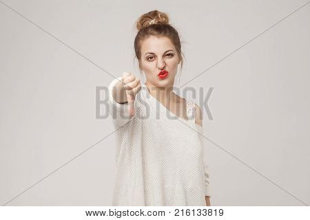 Bad sign. Woman demonstrate dislike at camera. Indoor shot poster