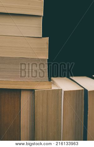 Books background. Old vintage books background. Education and knowledge, learn, study and wisdom concept. Stack of old books. Old books on a shelf. Stacked old books in vintage style.