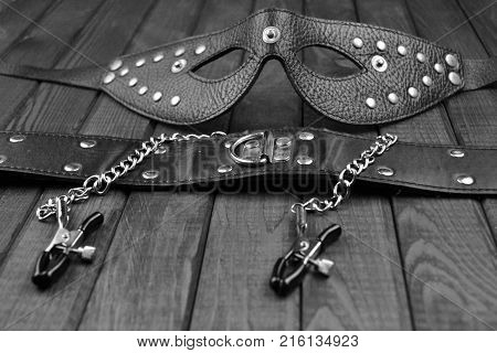 BDSM fetish sex toys bondage composition: leather mask, chain, neck collar, black and white art